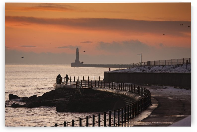Sunderland, Tyne And Wear, England; People Walking Along The Coast With A Lighthouse In The Distance by PacificStock