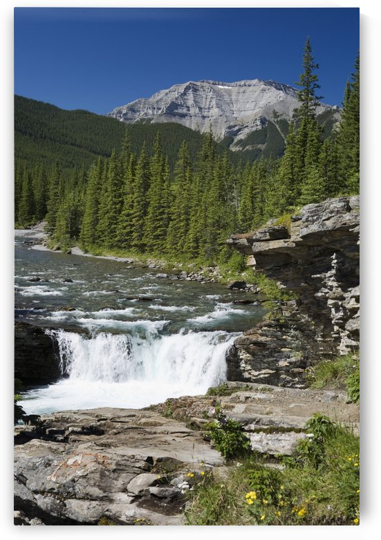 Waterfalls With Rock Ledge And Mountain In The Background; Alberta, Canada by PacificStock