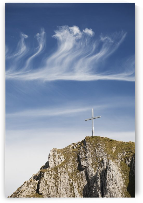 Mountain Peak With A Cross On Top Against A Blue Sky With Clouds; Fussen, Germany by PacificStock