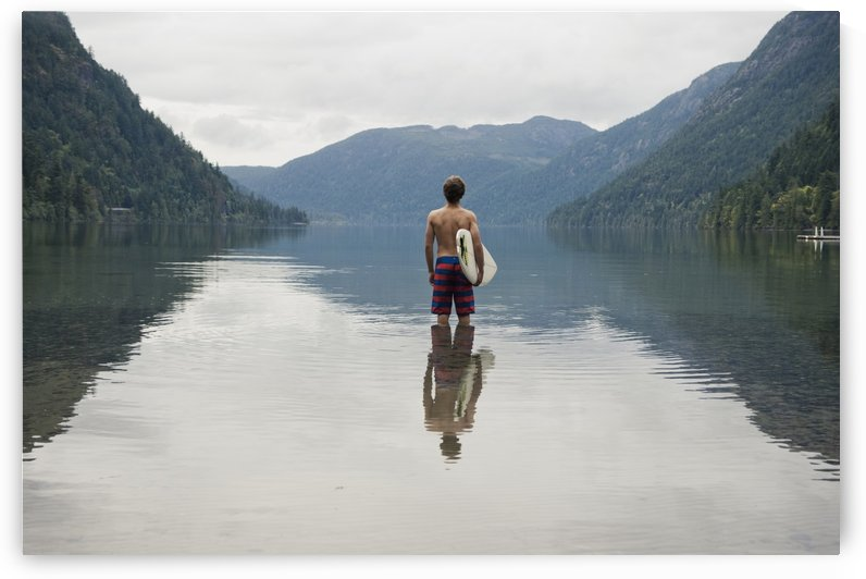 A Young Man Wearing A Swimsuit Stands In Cameron Lake; British Columbia Canada by PacificStock