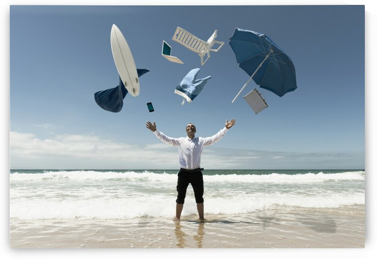 A Man Stands In The Ocean With Items From Work And Vacation Flying Over His Head; Tarifa, Cadiz, Andalusia, Spain by PacificStock