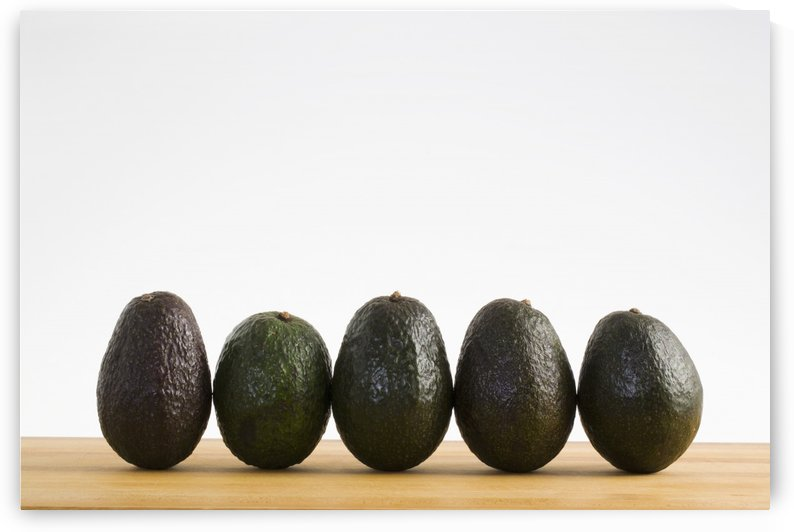 A Row Of Avocados Standing Upright On A Wooden Board; Calgary, Alberta, Canada by PacificStock