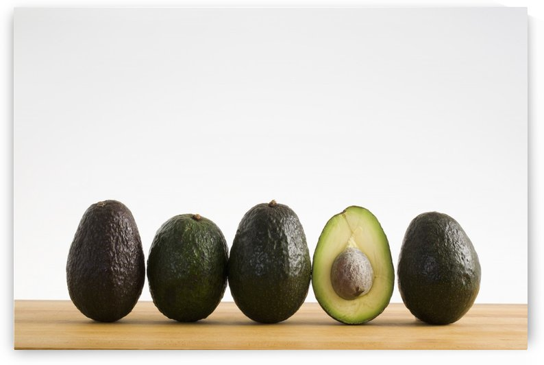 A Row Of Avocados Standing Upright On A Wooden Board With One Cut In Half With The Pit; Calgary, Alberta, Canada by PacificStock