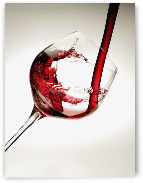 Red wine pouring into a glass by PacificStock