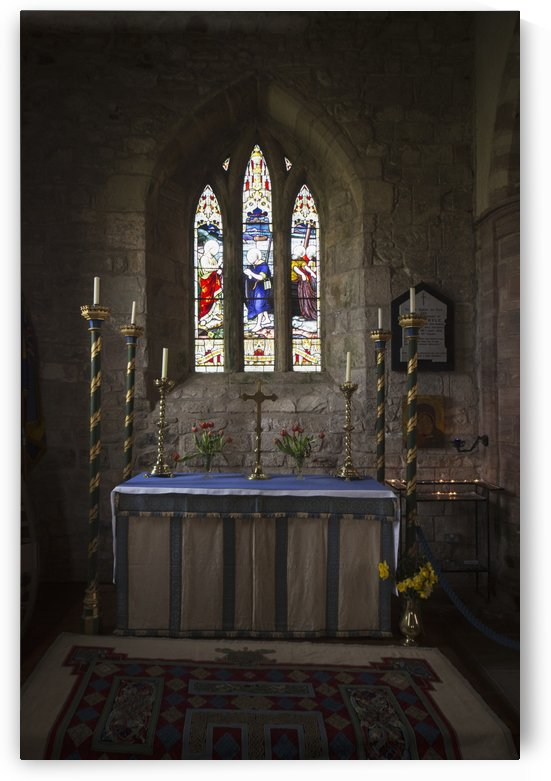 Stained glass windows and a table surrounded with candles in a church; Bamburgh, Northumberland, England by PacificStock
