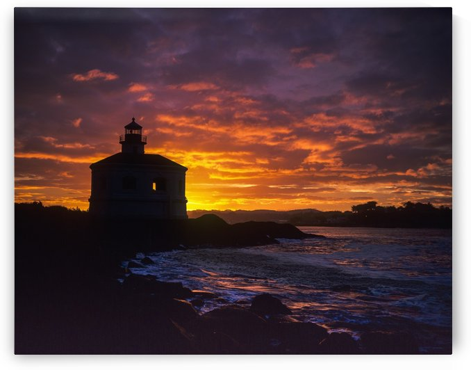 The sun rises behind the Coquille River Lighthouse; Bandon, Oregon, United States of America by PacificStock