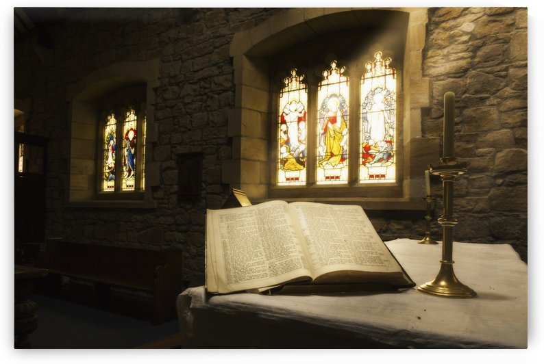 An open Bible on display in a church with colourful stained glass windows; Bamburgh, Northumberland, England by PacificStock