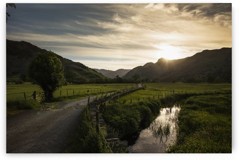 A gravel road between fields as the sun sets behind the mountains; Lake District, Cumbria, England by PacificStock