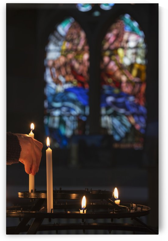 A man's hand lights a candle in a church with colourful stained glass window in the background; Northumberland, England by PacificStock