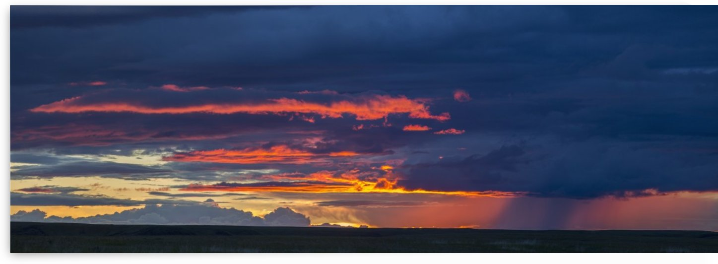 Panoramic vew of sunset lit clouds and a rain shower over Grasslands National Park; Saskatchewan, Canada by PacificStock