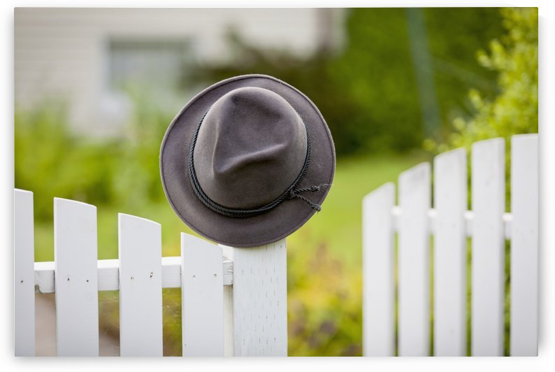 A hat hanging on the post of a white picket fence; Vancouver, British Columbia, Canada by PacificStock