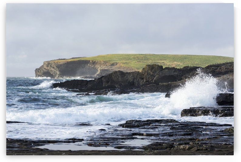Waves crashing into rocky coast with large grassy hill and cliffs in background; Kilkee, County Clare, Ireland by PacificStock