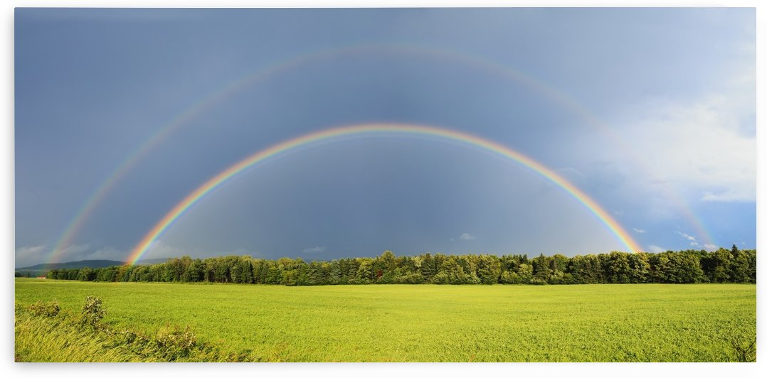 Double rainbow over trees and lush green field; Quebec, Canada by PacificStock