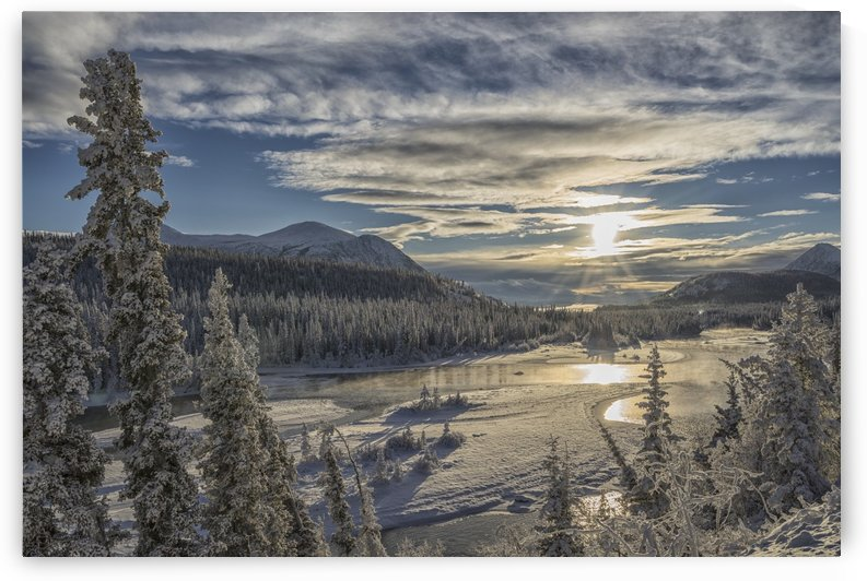 The sun breaks through the clouds above the Takhini River on a late winter afternoon, near Whitehorse; Yukon, Canada by PacificStock