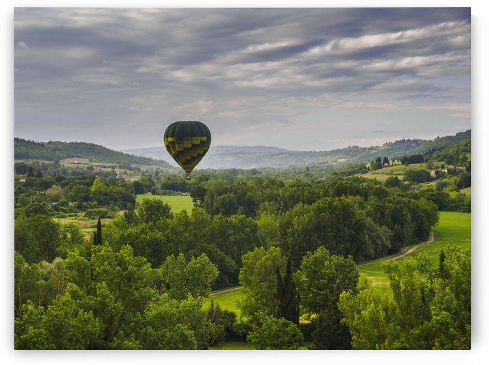 A hot air balloon flies low over a spring valley landscape; Tuscany, Italy by PacificStock