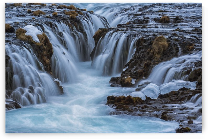 Turquoise water flowing over rocks into a river; Bruarfoss, Iceland by PacificStock