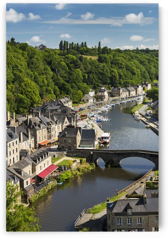 Treed valley riverside town, stone bridge and boats in the harbour with blue sky and clouds; Dinan, Brittany, France by PacificStock