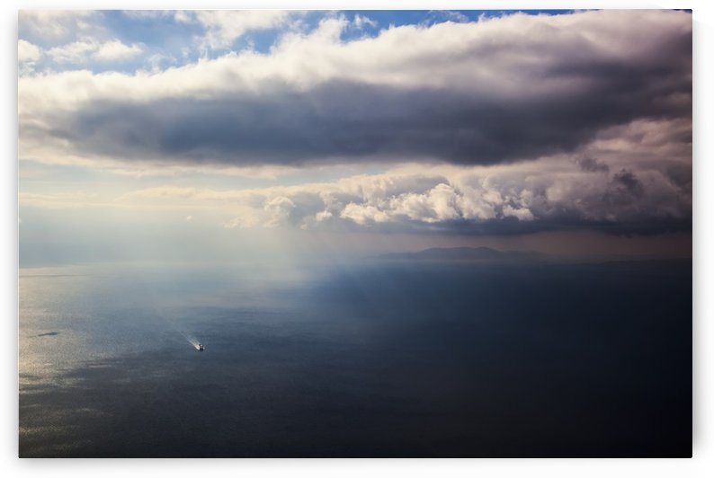 A lone boat on the Aegean sea under a cloudy sky and distant view of the coastline; Greece by PacificStock