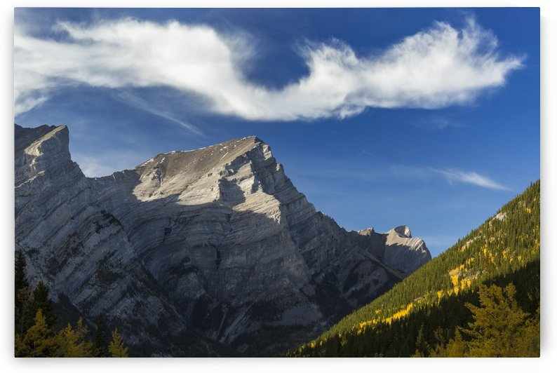 Close up of mountain peak lit by the sun in an alpine valley with autumn colours and an interesting cloud formation and blue sky, Kananaskis Provincial Park; Alberta, Canada by PacificStock