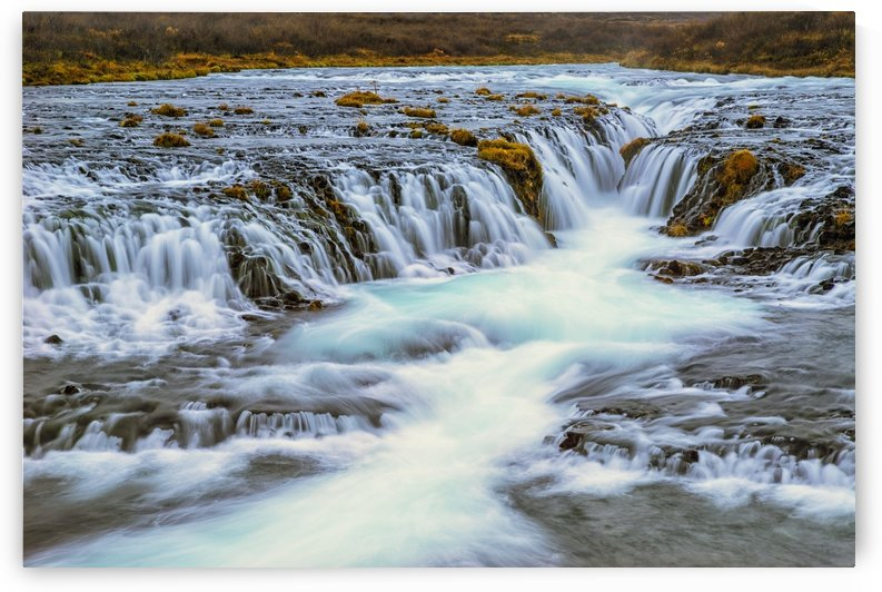 Water cascading over rocks and flowing into a river; Bruarfoss, Iceland by PacificStock