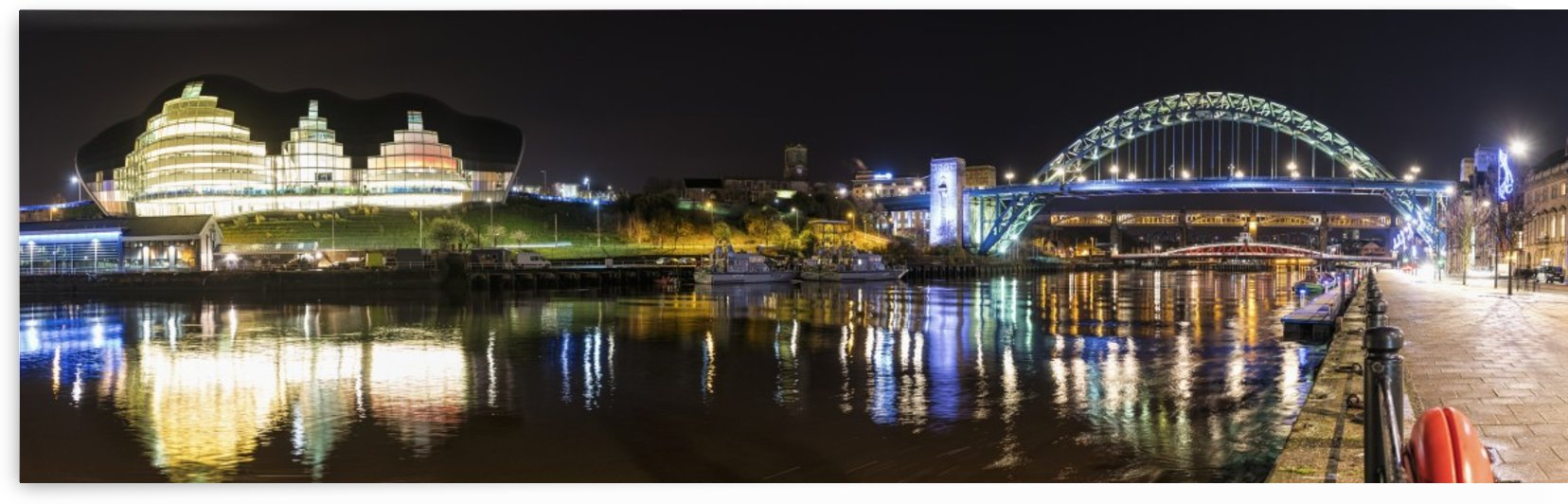 Tyne Bridge illuminated at nighttime over River Tyne and illuminated buildings; Newcastle, Tyne and Wear, England by PacificStock