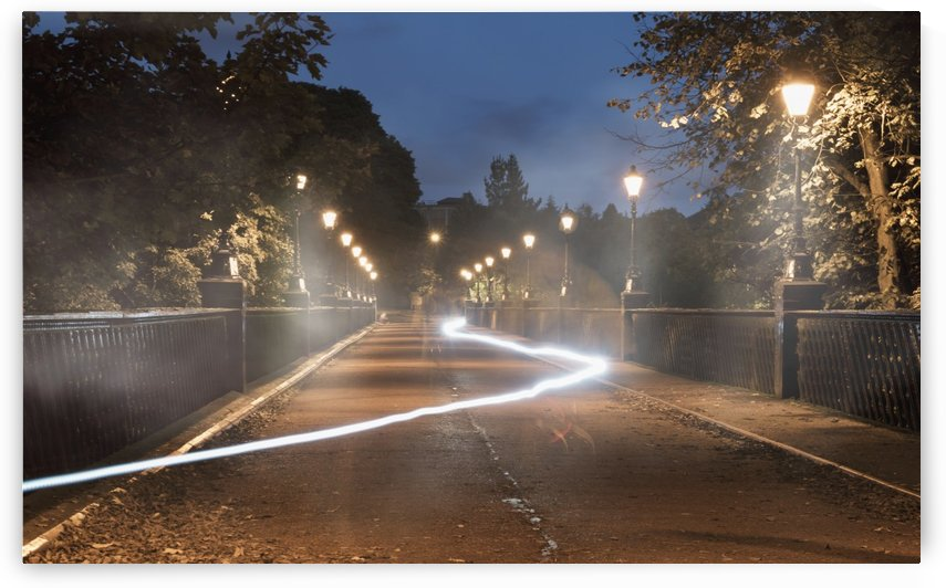Light trail glowing in a path lit by lamp posts at dusk; Newcastle, Tyne and Wear, England by PacificStock