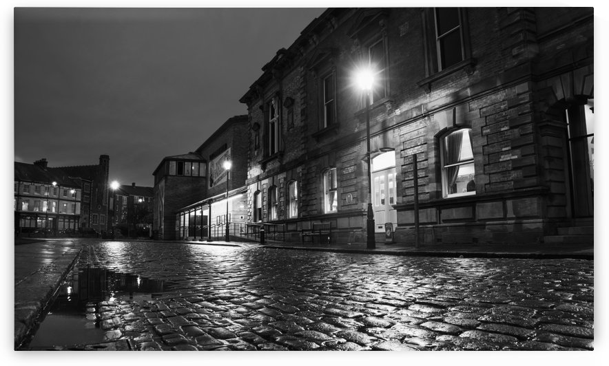 Light from a lamp post illuminating wet cobblestone road; South Shields, Tyne and Wear, England by PacificStock