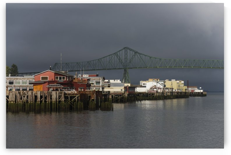 Sunlight warms the riverfront with storm clouds over the Astoria-Megler bridge; Astoria, Oregon, United States of America by PacificStock