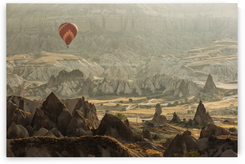 Hot air balloon flying over rock landscape at Cappadocia Turkey by MIRICA DAN-ALEXANDRU