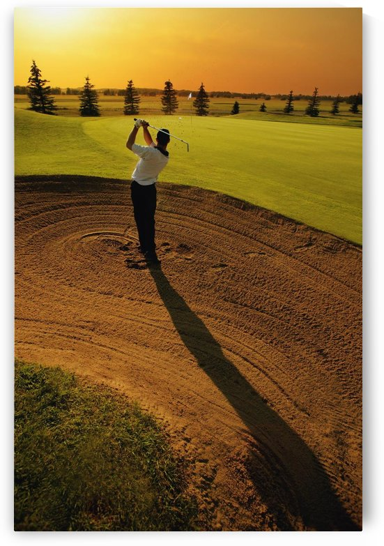 Golfer Taking A Swing From A Golf Bunker by PacificStock