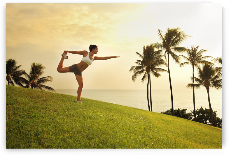 Hawaii, Oahu, Female Doing A Yoga Pose, Stretching On A Hill Overlooking Ocean, Palm Trees And Sunset. by PacificStock