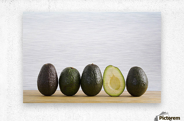 A Row Of Avocados Standing Upright On A Wooden Board With One Cut In Half Without The Pit; Calgary, Alberta, Canada  Metal print