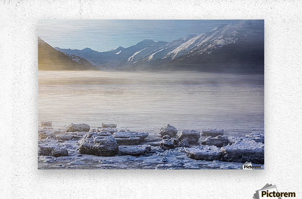 The sun shines through low altitude fog cast in warm light along Turnagain Arm and the Seward Highway, sea ice covering the ocean in the foreground, the Kenai Moutains revealed in the background, South-central Alaska; Alaska, United States of America  Metal print