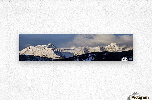 Panorama of snow covered mountains with early morning light, silhouetted forest in the foreground, blue sky and clouds; Kananaskis Country, Alberta, Canada  Metal print