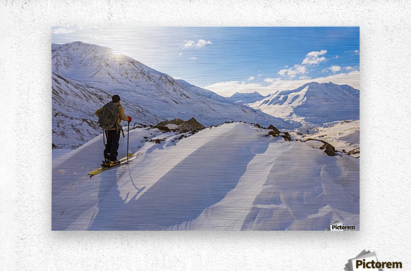 A backcountry skier looks over the Black Rapids Glacier valley from a high point on the terminal moraine in winter; Alaska, United States of America  Metal print