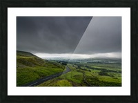 Dark storm clouds over a lush, green landscape and road; North Yorkshire, England Picture Frame print