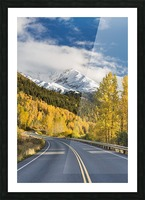 Snow-capped Kenai Mountains dwarf the Seward highway, trees covered in yellow leaves in autumn line the road, South-central Alaska; Seward, Alaska, United States of America Picture Frame print