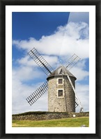 An old stone windmill on a hillside with wooden blades, surrounded by a stone fence with blue sky and clouds; Brehec, Brittany, France Picture Frame print