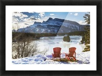 Two red chairs on snow covered ridge overlooking frozen lake with snow covered mountain in the background with blue sky and clouds; Banff, Alberta, Canada Picture Frame print