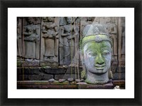 A terra cotta head of buddha sits in front of bas-relief in a terra cotta garden; Chiang Mai, Thailand Picture Frame print
