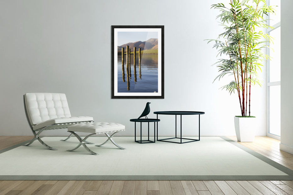 Wooden posts reflected in tranquil after with mountains the the background; Keswick, Cumbria, England in Custom Picture Frame