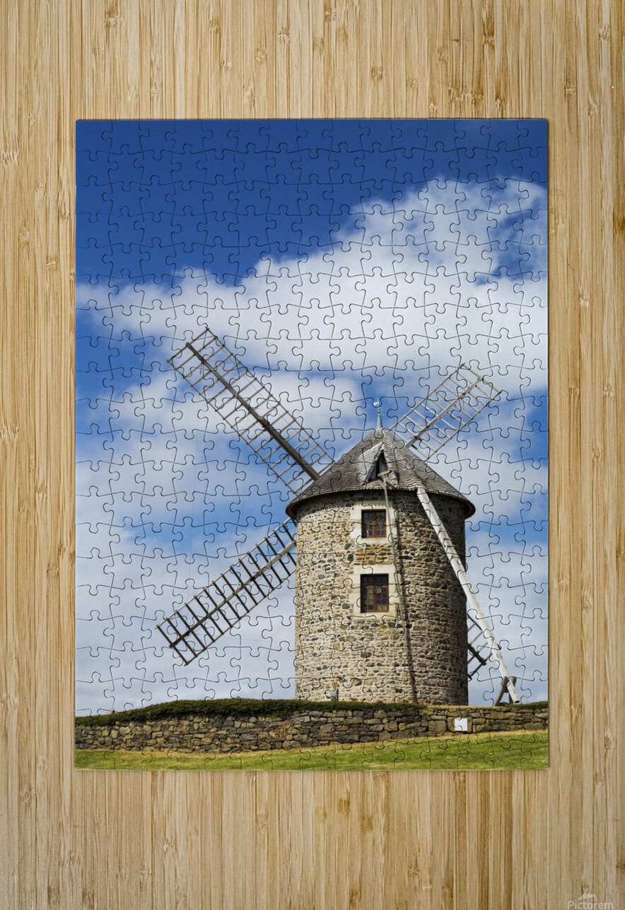 An old stone windmill on a hillside with wooden blades, surrounded by a stone fence with blue sky and clouds; Brehec, Brittany, France  HD Metal print with Floating Frame on Back