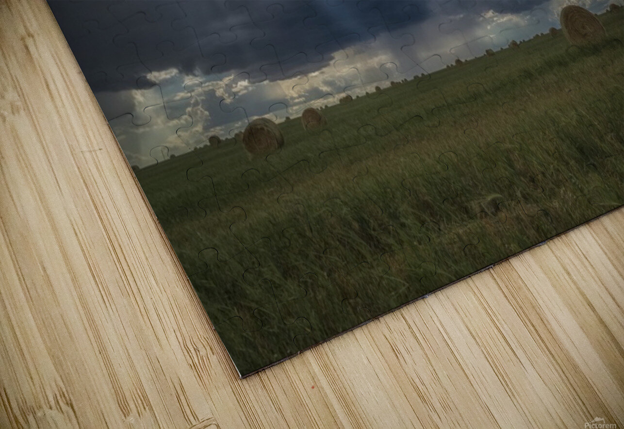 Sunlight breaks through the storm clouds over a field of hay bales; Saskatchewan, Canada HD Sublimation Metal print