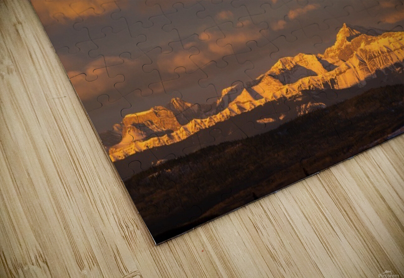 Glowing warmly lit snow covered mountain range and foothills with glowing clouds and blue sky at sunrise; Calgary, Alberta, Canada HD Sublimation Metal print