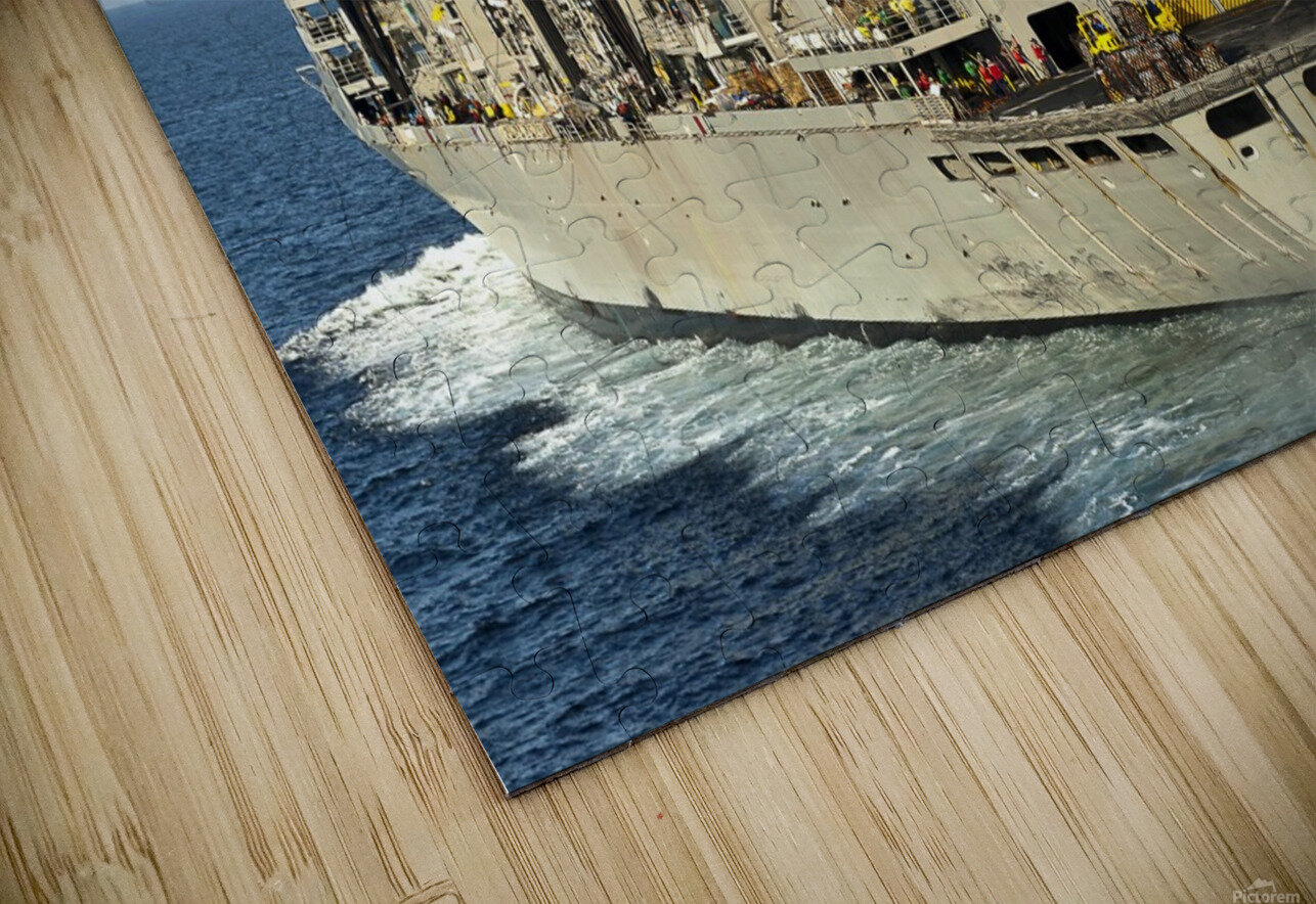 An MH-60S Knighthawk lifts cargo from the fast combat support ship USNS Rainier. HD Sublimation Metal print