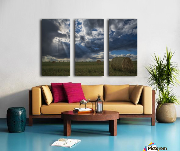 Sunlight breaks through the storm clouds over a field of hay bales; Saskatchewan, Canada Split Canvas print