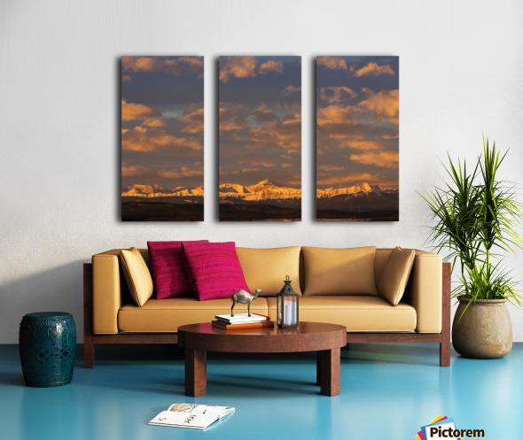 Glowing warmly lit snow covered mountain range and foothills with glowing clouds and blue sky at sunrise; Calgary, Alberta, Canada Split Canvas print