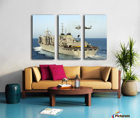 An MH-60S Knighthawk lifts cargo from the fast combat support ship USNS Rainier. Split Canvas print