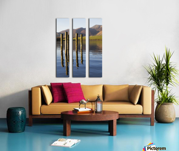 Wooden posts reflected in tranquil after with mountains the the background; Keswick, Cumbria, England Split Canvas print