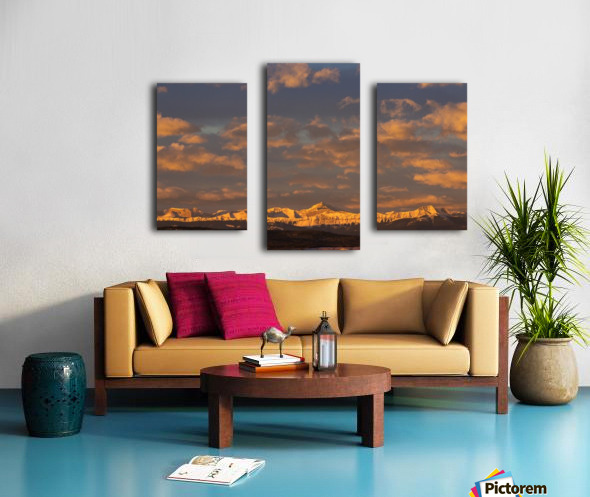 Glowing warmly lit snow covered mountain range and foothills with glowing clouds and blue sky at sunrise; Calgary, Alberta, Canada Canvas print